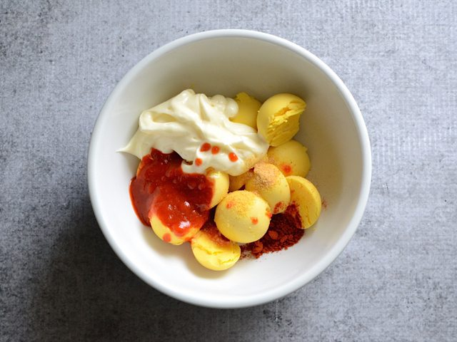 Egg yolks and spices in mixing bowl