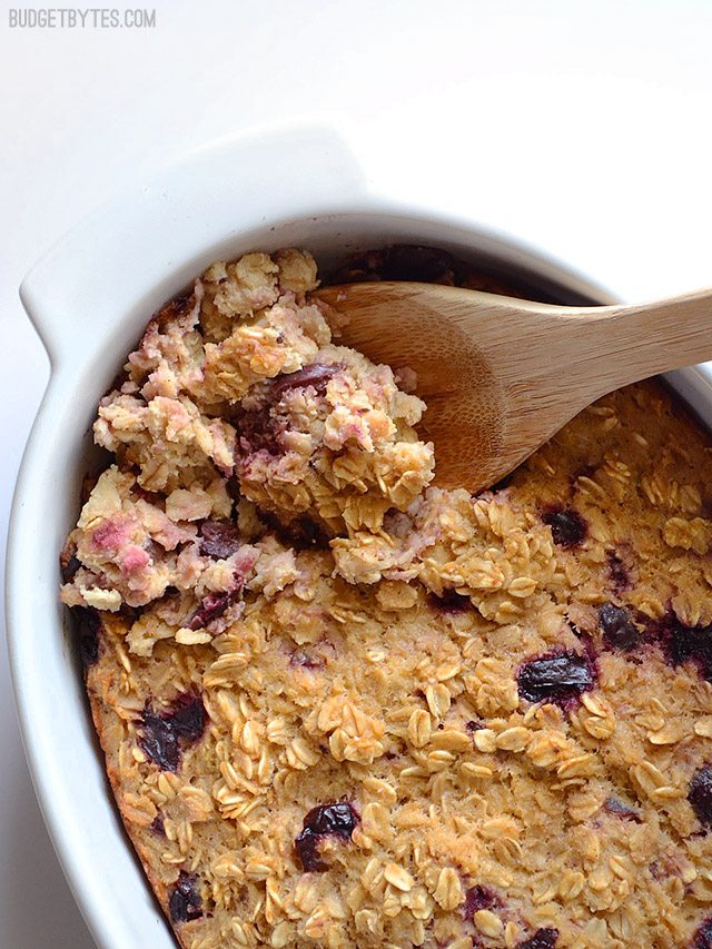 Close up of Apple Cherry Baked Oatmeal being scooped out of dish with wooden spoon