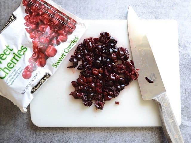 Bag of sweet cherries with some poured onto cutting board and chopped with knife