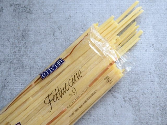 Dry fettuccine package, open, some pasta coming out