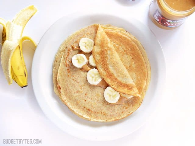 Homemade Crepes on plate with peanut putter and banana on top