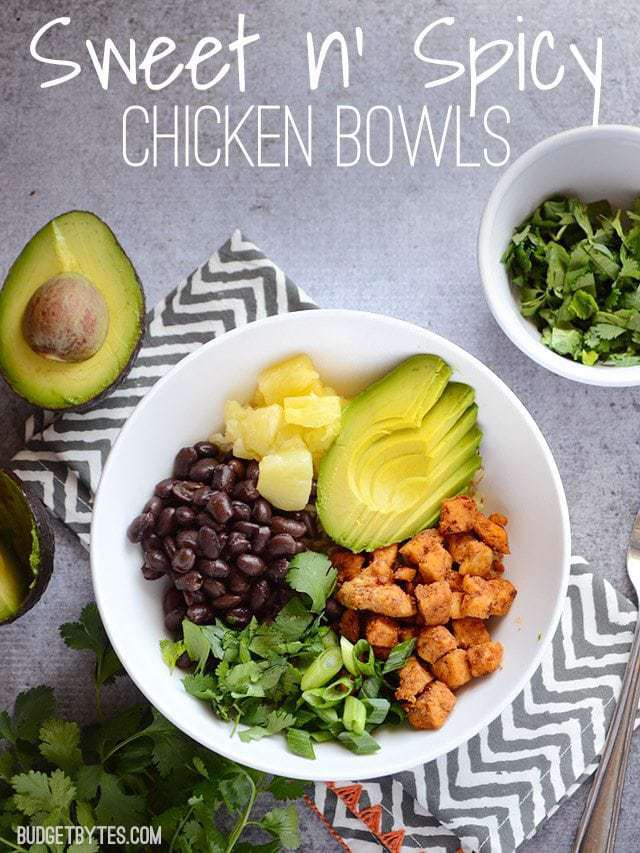 Top view of a Sweet n Spicy Chicken Bowl sitting on a gray and white chevron napkin, topping ingredients on side