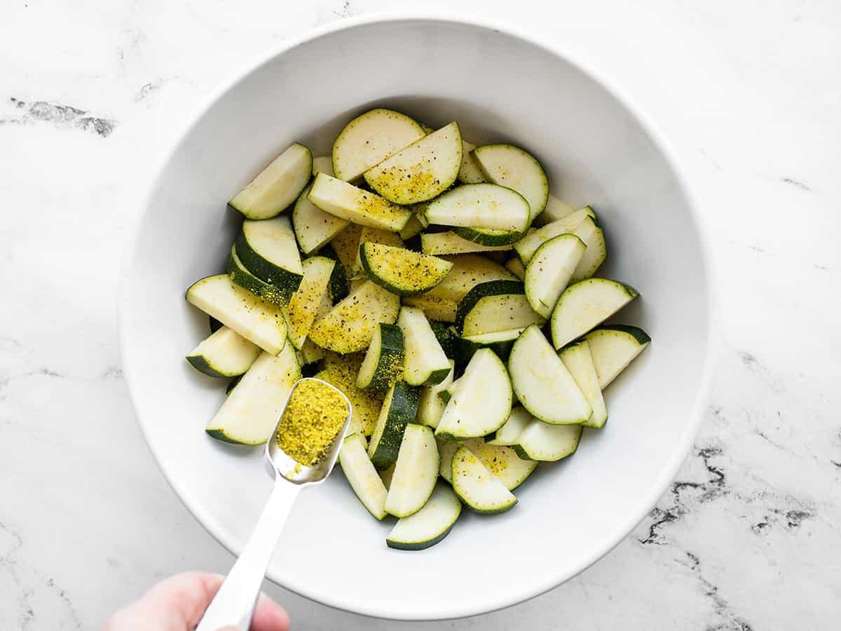 lemon pepper being sprinkled over the zucchini