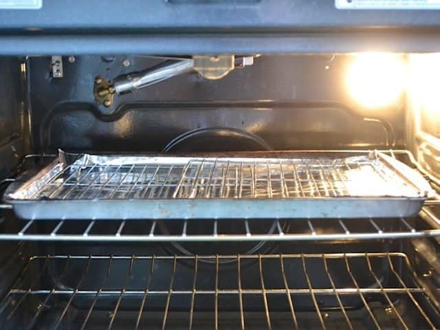 Sheet pan fitted with wire cooling racks in the oven close to the broiler