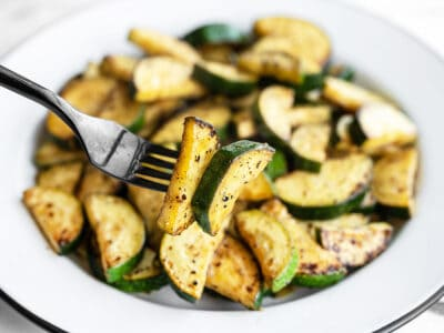 Close up of a forkful of lemon pepper zucchini with the bowl in the background