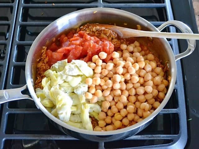 Add Tomatoes Chickpeas and Artichokes to the skillet