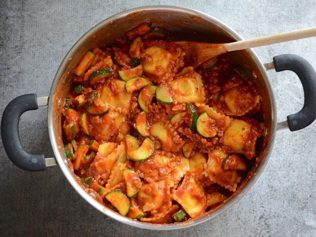 Ravioli stirred into the pot with sauce, sausage, and vegetables
