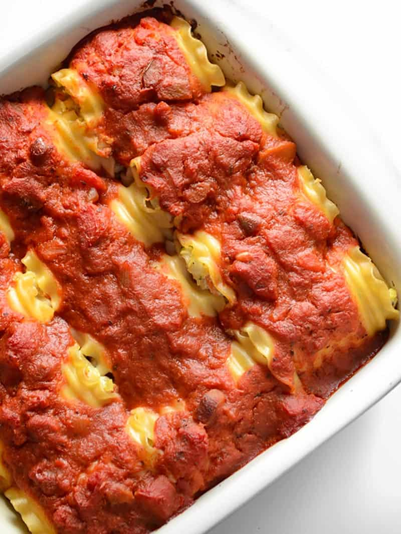 Overhead view of garden vegetable lasagna roll ups in a casserole dish