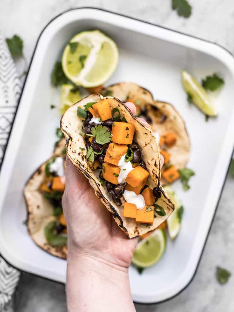 A hand holding a sweet potato taco close to the camera