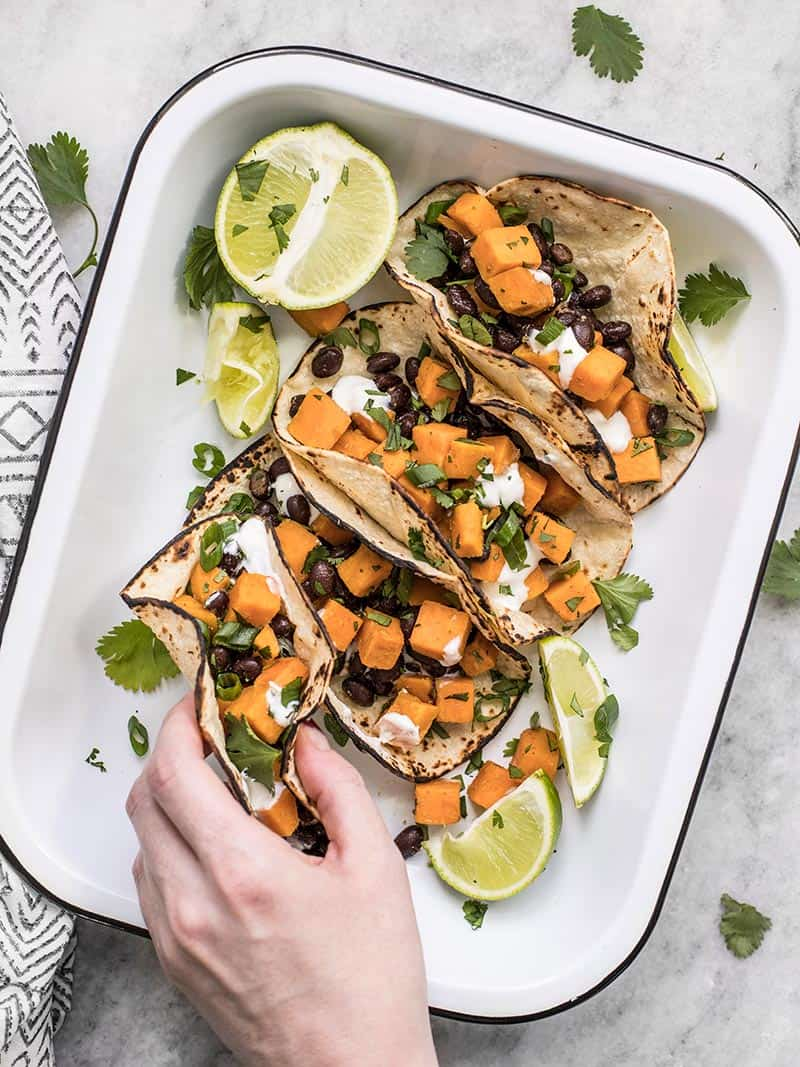 A hand picking up a sweet potato taco out of the serving dish