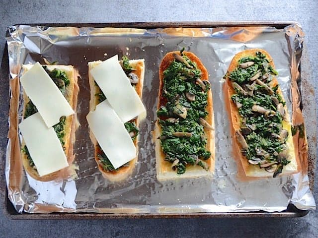 Slices of Swiss cheese added on top of spinach and mushroom bread