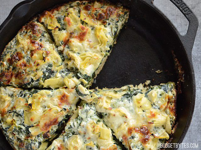 Close up of the baked and sliced Creamy Spinach Artichoke Pizza, with one slice missing