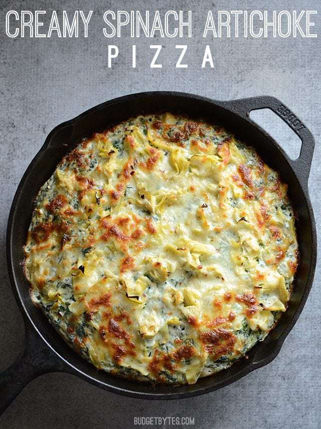 Overhead view of a Creamy Spinach Artichoke Pizza cooked in a cast iron pan, title text at the top