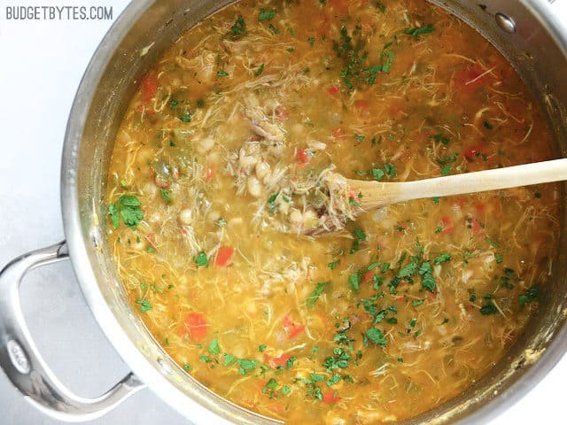Creole White Beans with Chicken in the pot with a wooden spoon