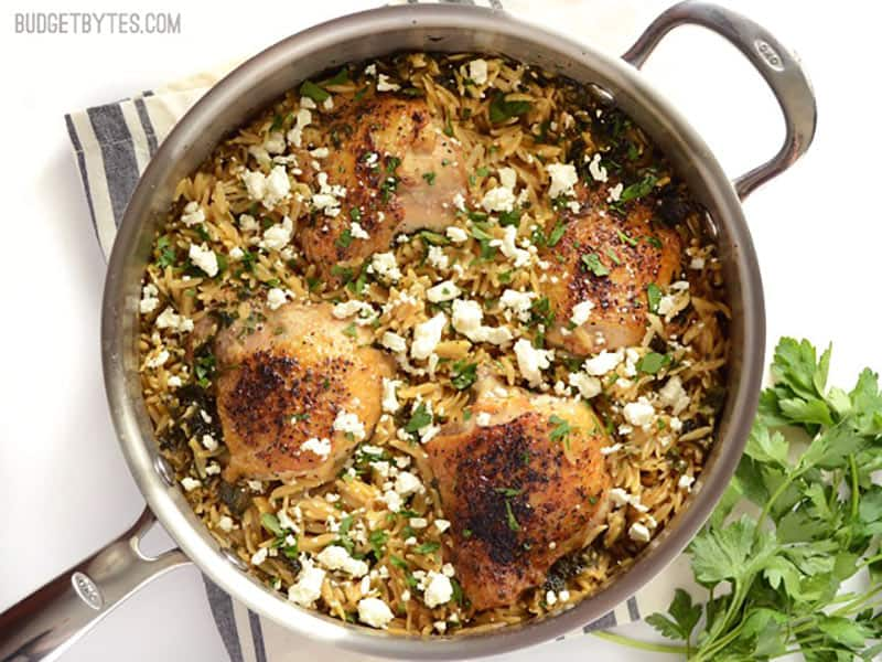 Overhead view of finished lemon pepper chicken with orzo in the skillet