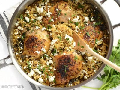 Overhead view of lemon pepper chicken with orzo in the skillet with a wooden spoon