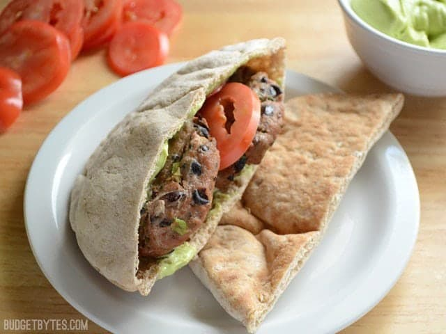 Mini Black Bean Turkey Burgers stuffed into a pita with tomato and avocado sauce
