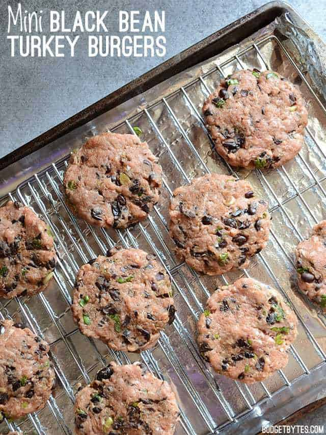 Unbaked Mini Black Bean Turkey Burgers on a baking sheet fitted with wire cooling racks
