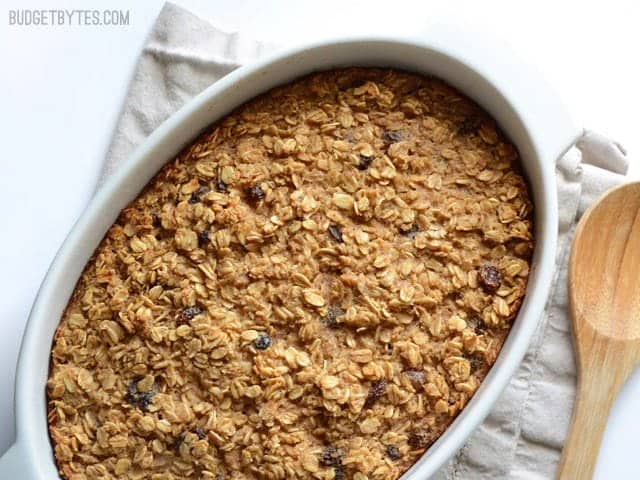 """""""Oatmeal Cookie Baked Oatmeal finished, in the casserole dish, wooden spoon on the side"""