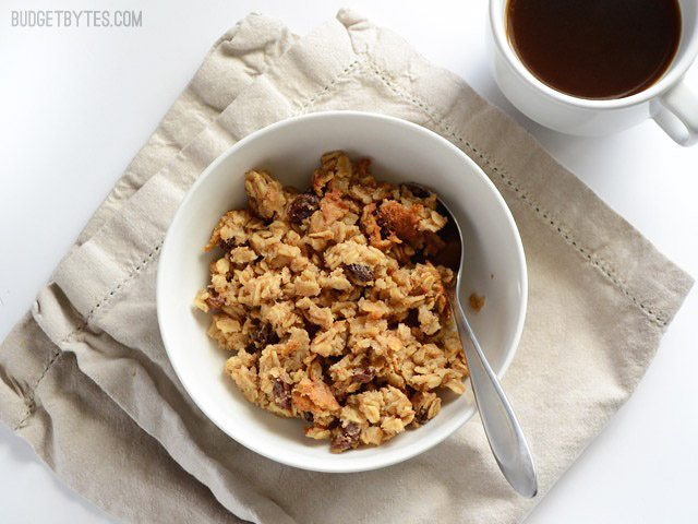 A bowl of oatmeal cookie baked oatmeal on a napkin with a mug of coffee on the side