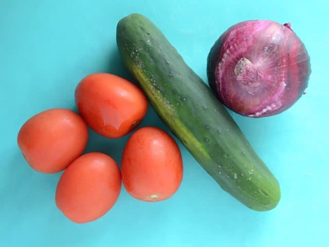 Tomato Cucumber and Red Onion on a blue cutting board