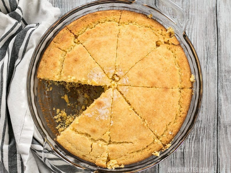 Homemade cornbread baked in a pie plate with one slice missing.