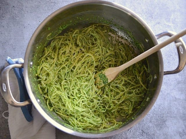 Pasta tossed and fully coated in pesto