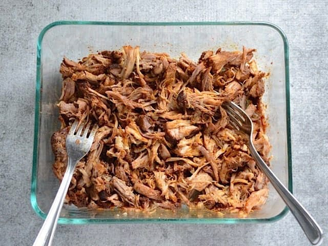 Shredded Chili Rubbed Pulled Pork in a glass dish with two forks