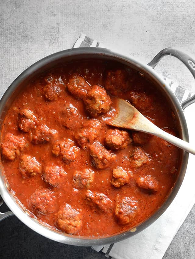 Overhead view of meatballs in sauce in the skillet with a wooden spoon