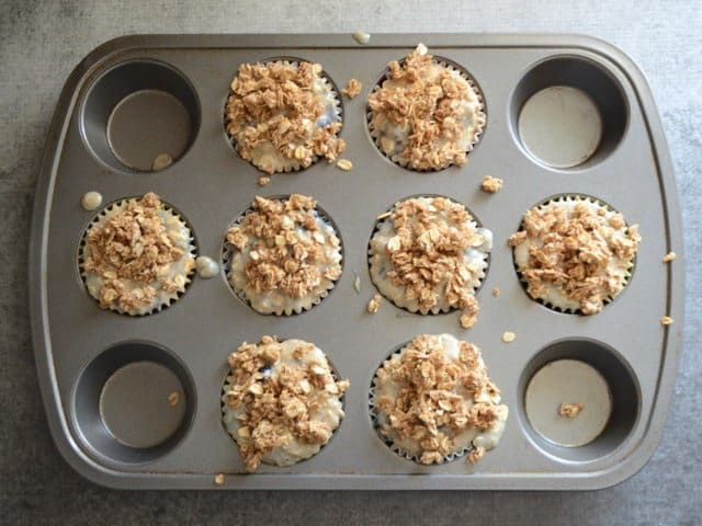 Muffin tin filled with batter and topped with crumble