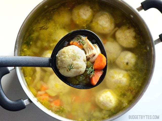 Close up of a label full of Matzo Ball Soup being held over the pot