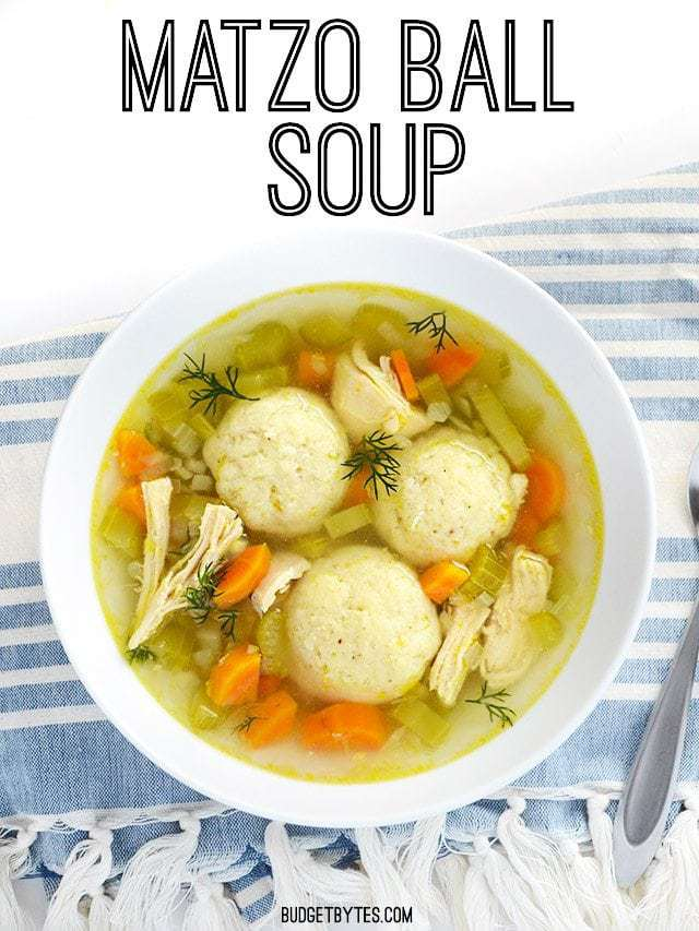 Top view of a bowl of Matzo Ball Soup sitting on a blue and white stripped napkin