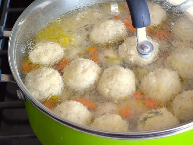 Simmering Matzo Balls in pot with veggies and broth