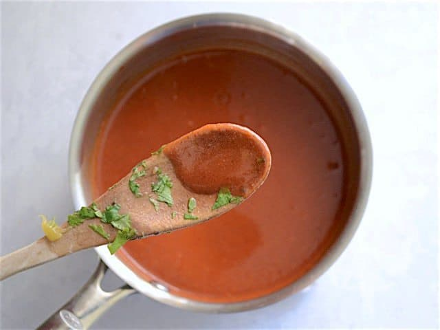 Thickened Enchilada Sauce on a wooden spoon