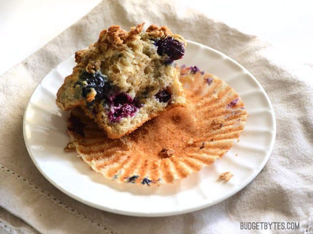 A half eaten Triple Berry Oatmeal Muffin on a plate