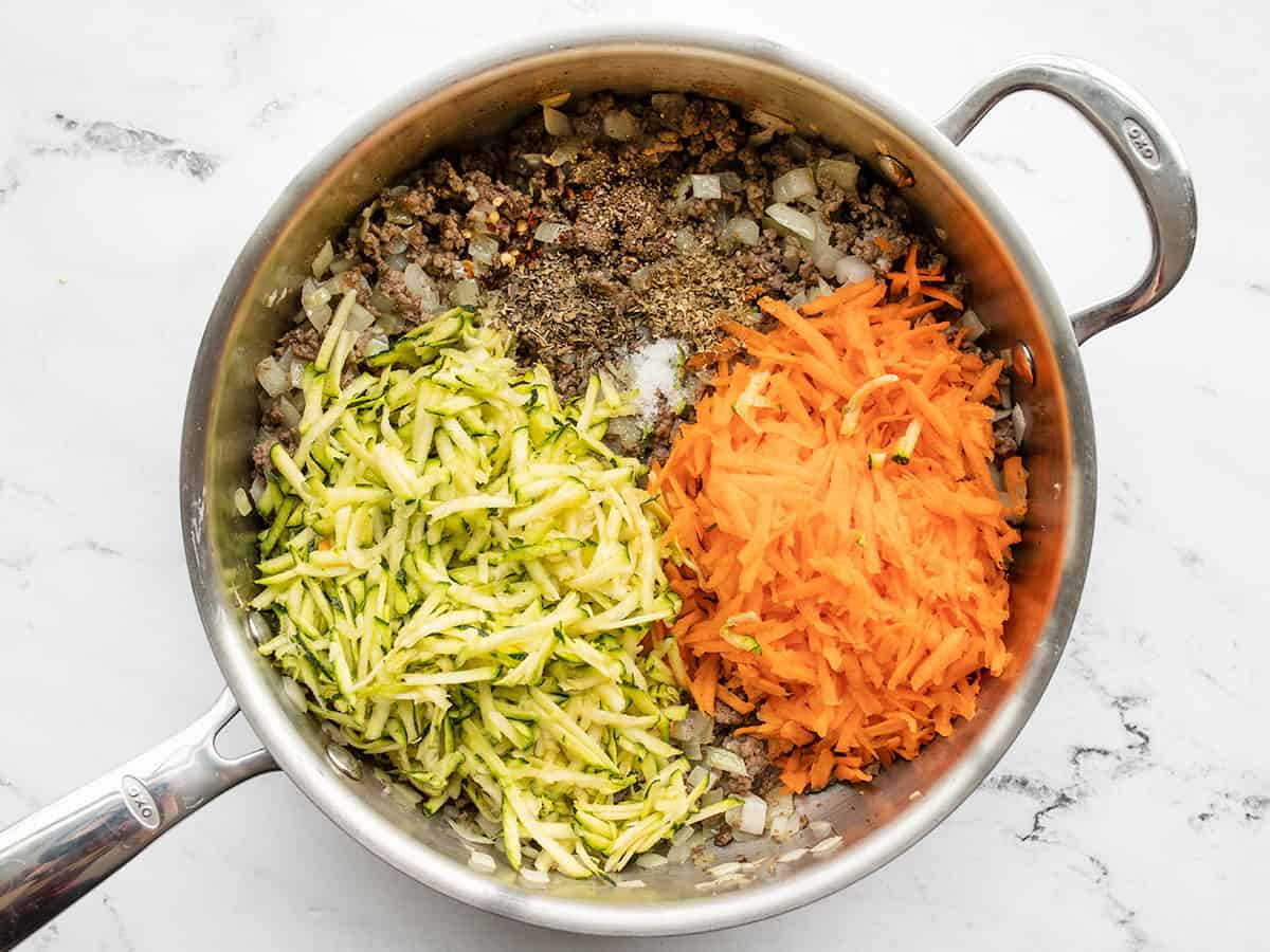 Shredded vegetables added to the skillet with the meat