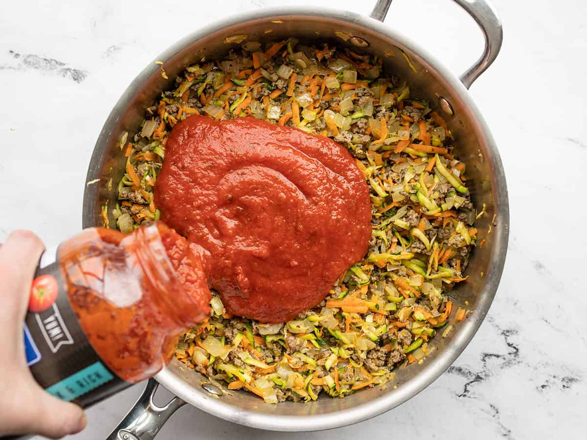 Pasta sauce being poured into the skillet with the meat and vegetables
