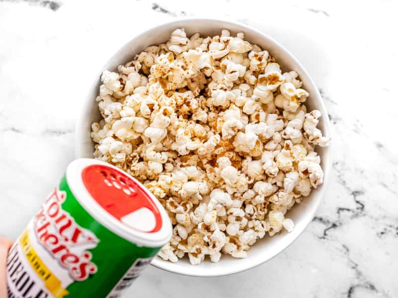 Sprinkle seasoning salt onto buttered popcorn.