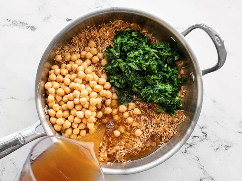 Chickpeas, spinach, broth, and lemon juice added to the skillet