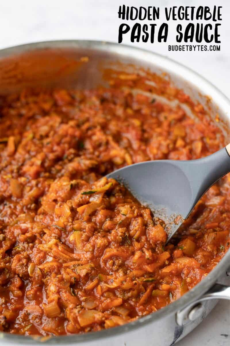 CLose up side view of pasta sauce in a skillet with a spatula, title text at the top
