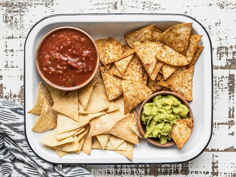A baking dish full of Homemade Baked Tortilla Chips with bowls of salsa and guacamole