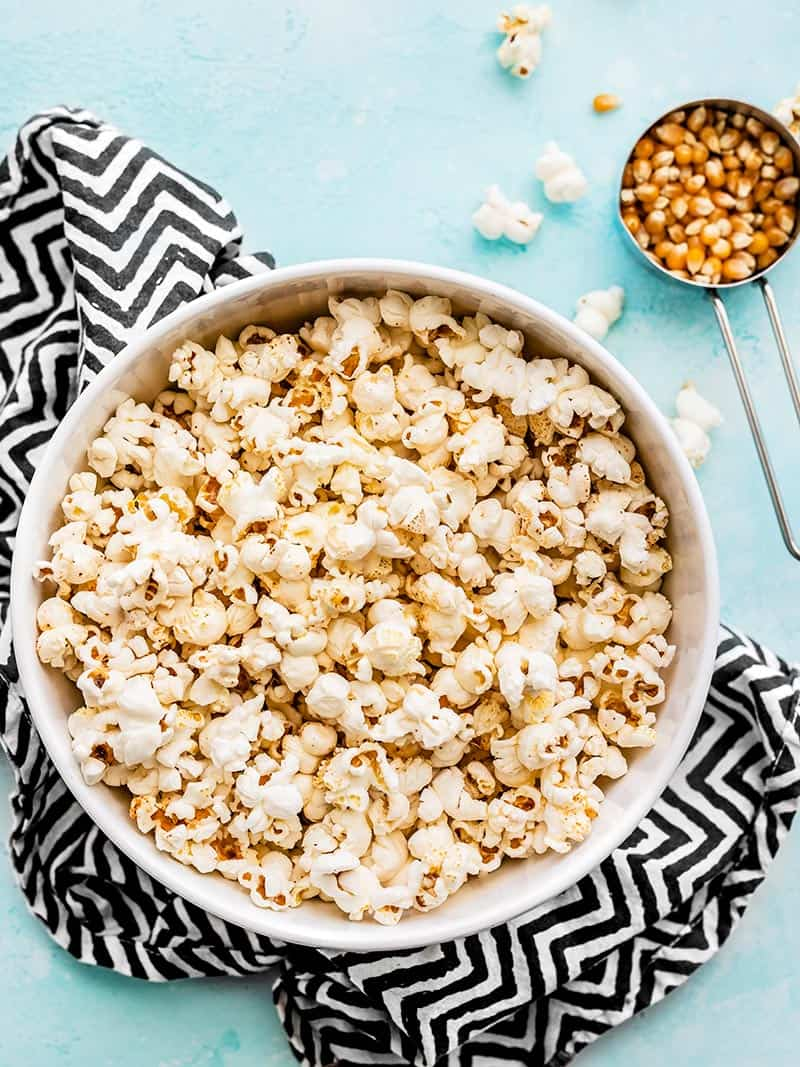 A big bowl of stovetop popcorn on a zig zag napkin with a measuring cup of unpopped kernels on the side