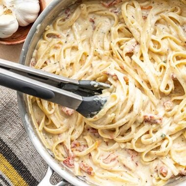 Overhead view of creamy pasta twirled around the tongs in the skillet.