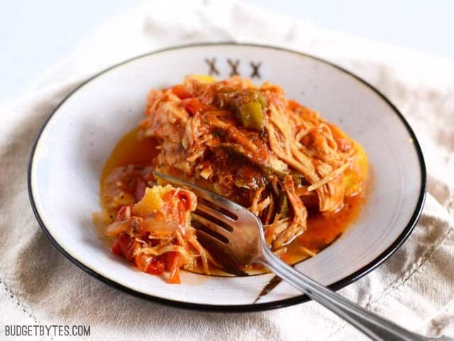 Slow Cooker Italian Chicken and Peppers on polenta with a fork taking a bite
