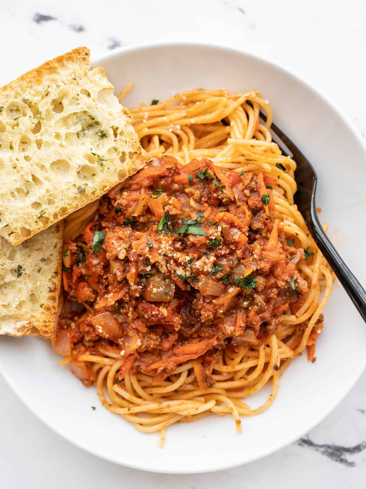 Overhead view of a bowl of spaghetti with hidden vegetable pasta sauce and garlic bread on the side