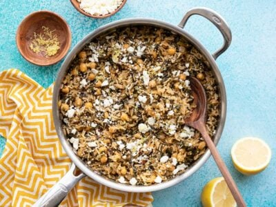 Skillet full of Spinach and Chickpea Rice Pilaf next to a cut lemon and small dish of feta, on a blue background