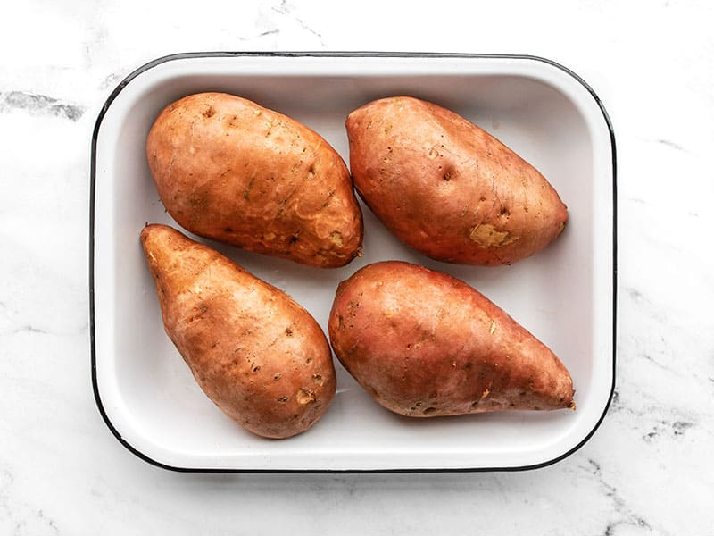 Sweet potatoes in a baking dish rubbed in oil and pricked with a fork
