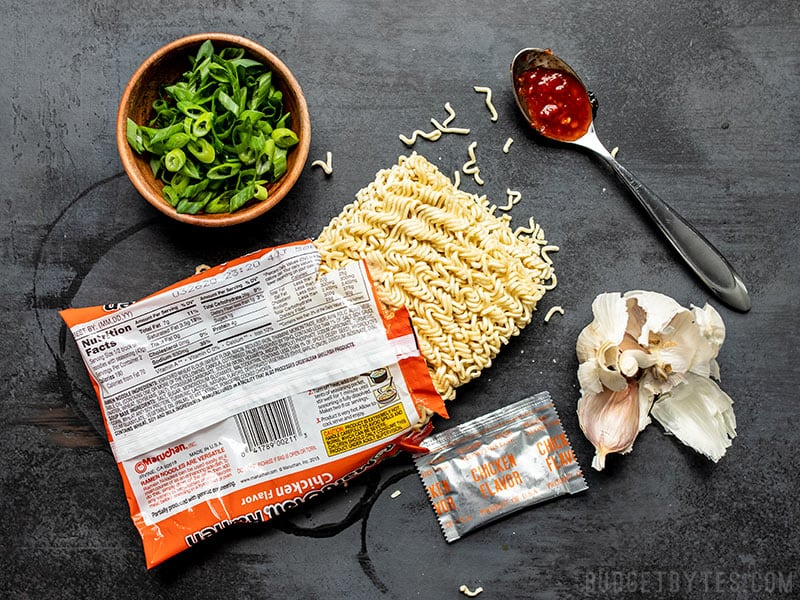 An opened package of instant ramen with other ingredients around it, including green onions, chile paste, and garlic.