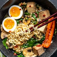 Close up of Chopsticks lifting noodles out of an upgraded bowl of instant ramen, with a soft boiled egg.