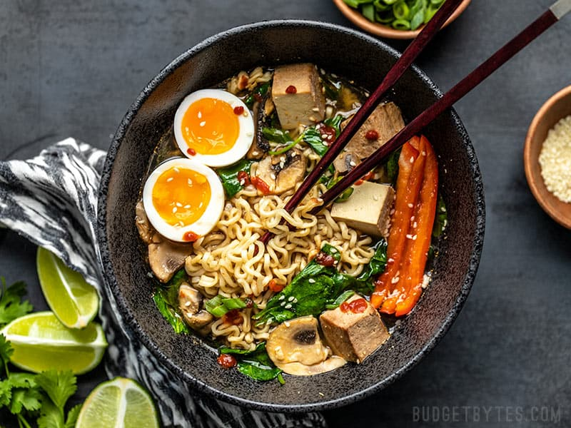 An upgraded bowl of instant ramen, viewed from above, being eaten with chopsticks